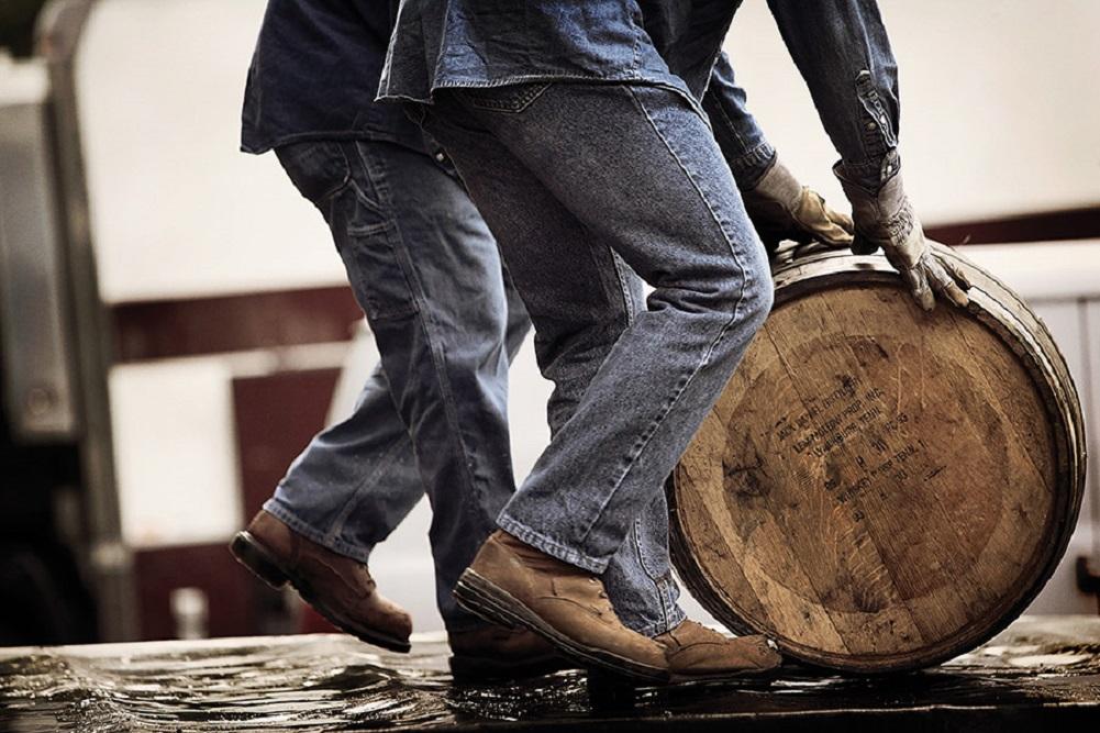 Two people in jeans pushing an oak barrel along the floor.