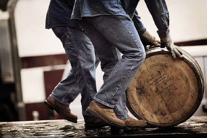 Two people in jeans pushing an oak barrel along the floor.