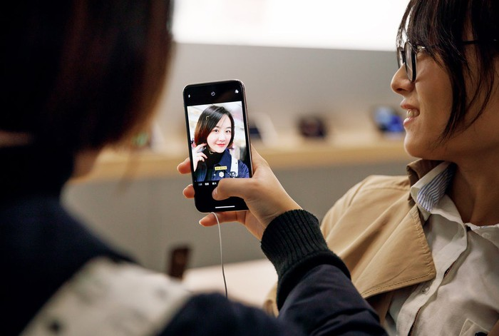 Chinese women using iPhone X in an Apple Store