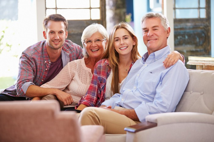 Older parents sitting on a couch with their two adult children