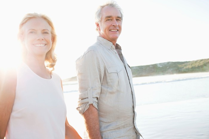Senior couple smiling as they walk by the water