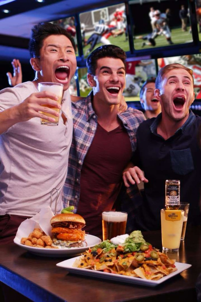 Three young men drinking beer and eating hamburgers and nachos in the sports bar area of a Dave and Buster's.