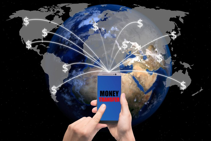 A person using a smartphone to initiate a money transfer to various parts of the world.