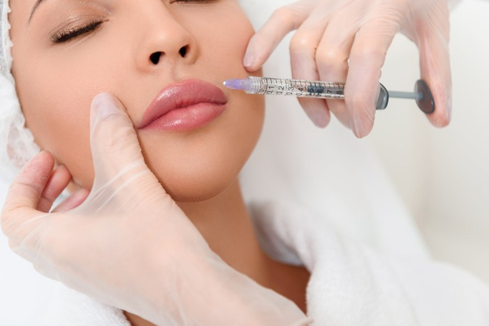 Woman getting injected by needle in face