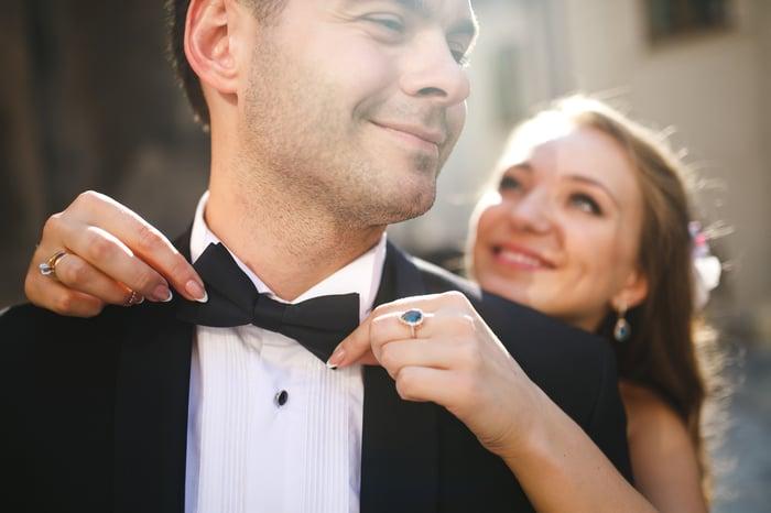 Woman tying a bowtie on a man in a tuxedo