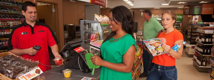 Several customers stand at the checkout counter of a 7-Eleven.