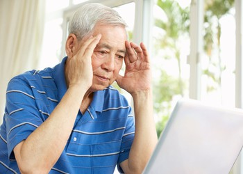 senior male holding his head while looking at a laptop_GettyImages-159302419