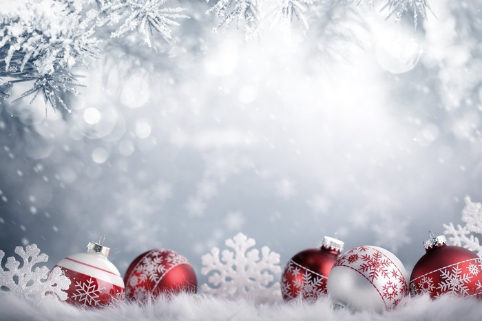Red and white holiday ornaments with snow-covered branches in the background.