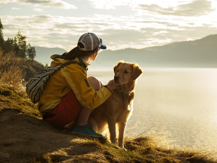 Girl hiking on a trail with a dog.