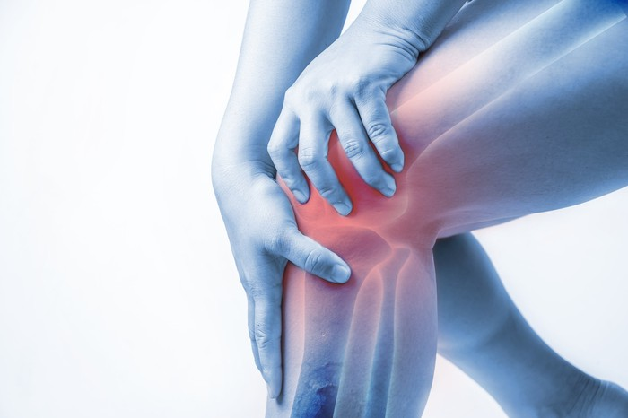 Person gripping knee in pain.