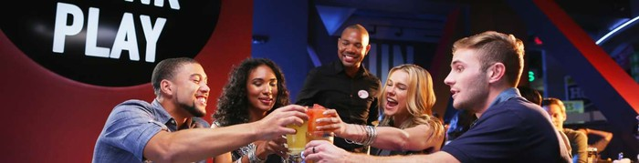 A group of raising beer glasses in a toast at Dave & Buster's.