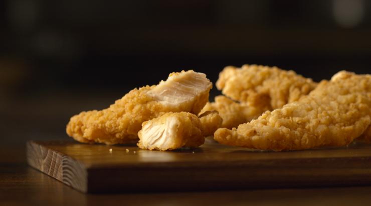 Golden crispy fried buttermilk tenders on a dark wooden chopping board.