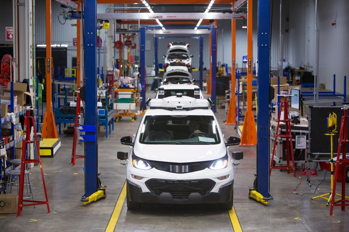 A line of white Chevrolet Bolt EVs with visible self-driving sensor hardware awaiting final assembly at GM's Orion Assembly Plant in Orion Township, Michigan.