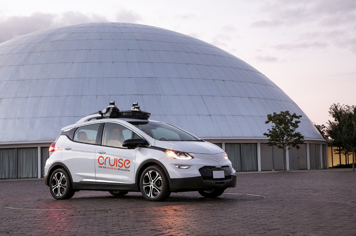 A white Chevrolet Bolt EV with Cruise Automation logos and visible self-driving hardware is parked next to the Design Dome on GM's historic Technical Center campus in Warren, Michigan.