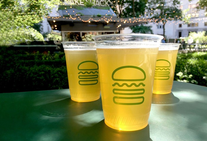 Three drinks in Shake Shack cups on a green table, with a Shake Shack restaurant in the background.