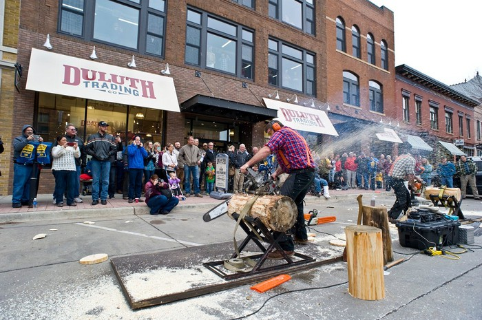 Person in a flannel shirt with a chainsaw cutting a log in front of a Duluth Trading store, with a modest audience of onlookers.