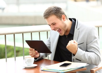 AG excited businessman with tablet and phone
