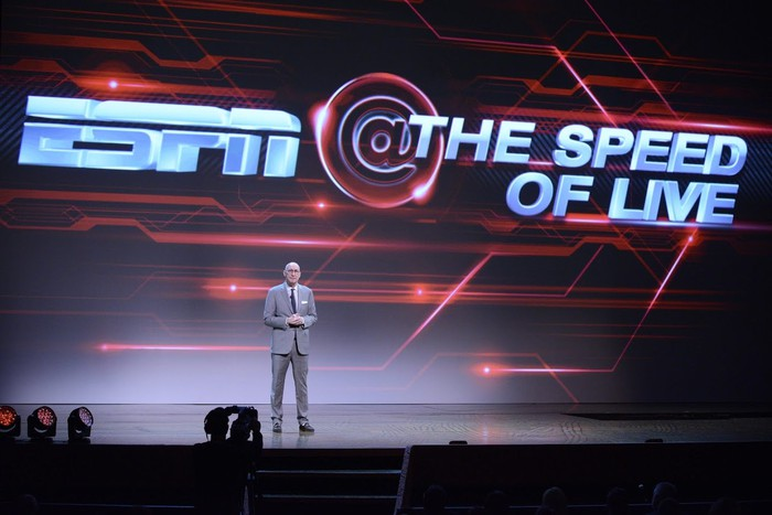 A man standing on stage in front of a screen that says ESPN @ The Speed of Live