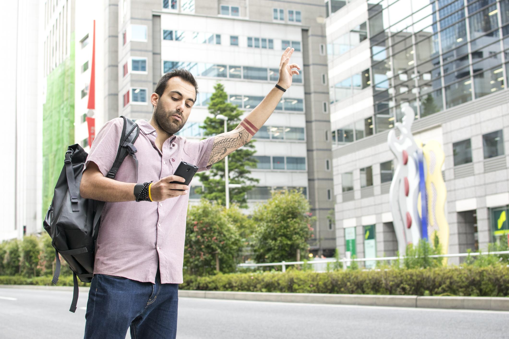 Man using smartphone for ridehailing
