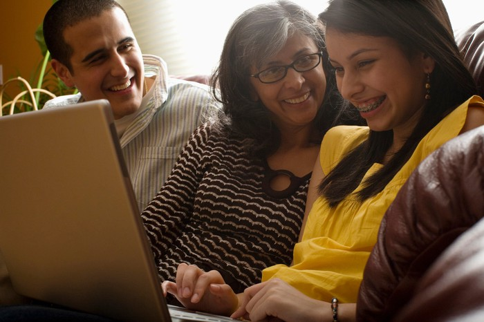 Mom and children sitting on couch laughing with daughter using laptop.