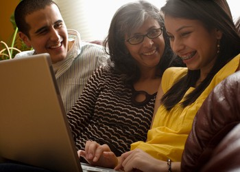 Mom and children sitting on couch laughing with daughter using laptop