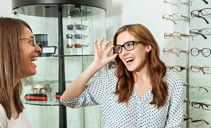 A woman smiling at a friend tries on a pair of glasses in an optical.