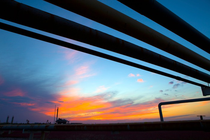 Oil pipelines overhead with the sun setting in the background.