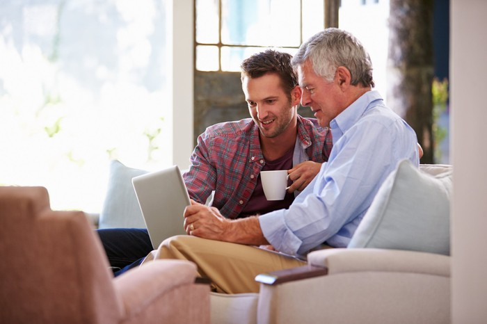 An older man and a youger man sit on a couch looking at a laptop.