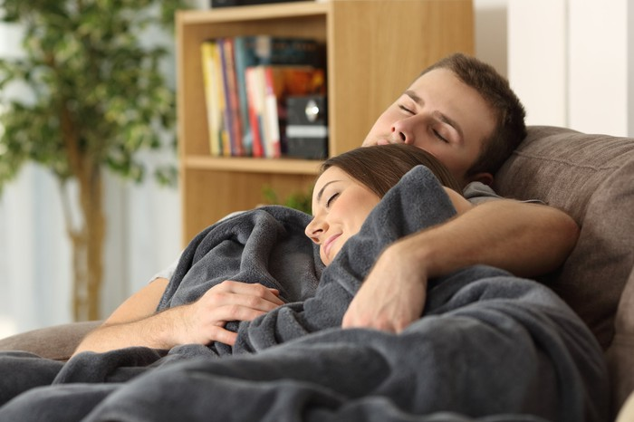 A young couple, snuggling and asleep on the couch.