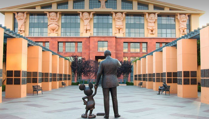 Satue of Wal Disney holding Mickey's hand from the back at Disney headquarters.