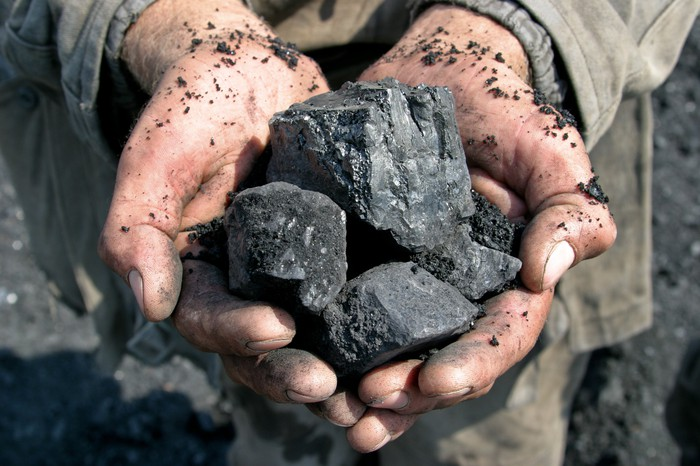 A miner holding chunks of coal in his hands.