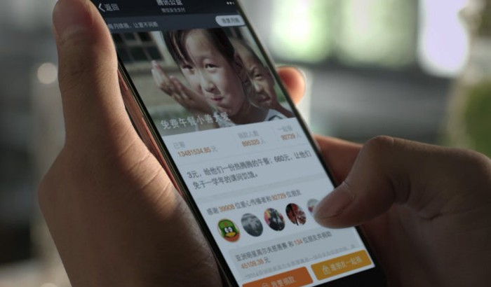 A closeup of someone using a smartphone on which one of Tencent's apps is showing.