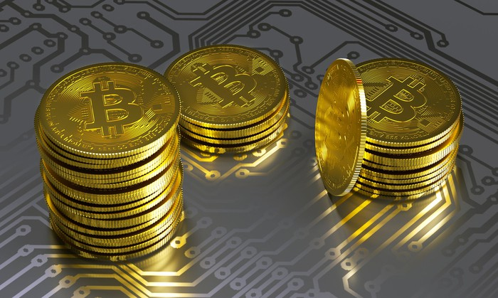 Physical gold bitcoin stacks lying atop a gray circuit board.