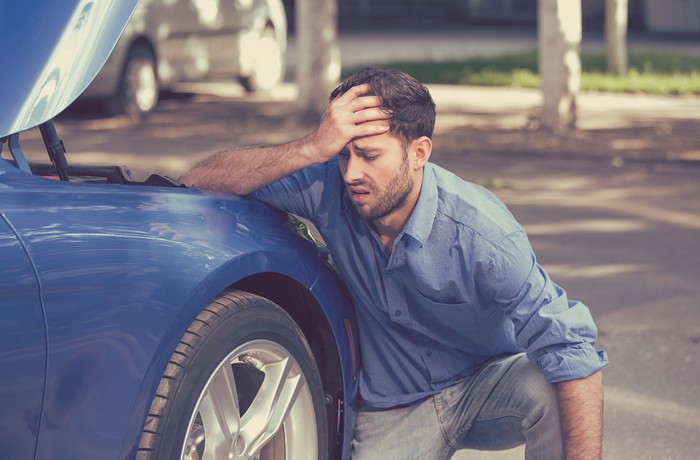 Man holding his head in exasperation while kneeling next to a car with its hood raised.