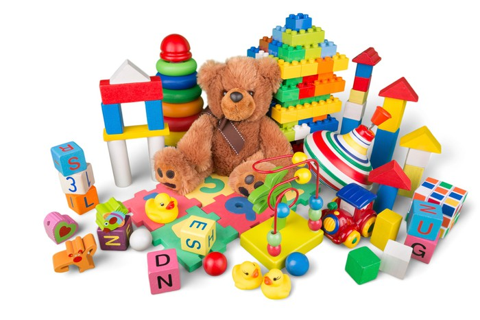 A collection of children's toys including a teddy bear and blocks.