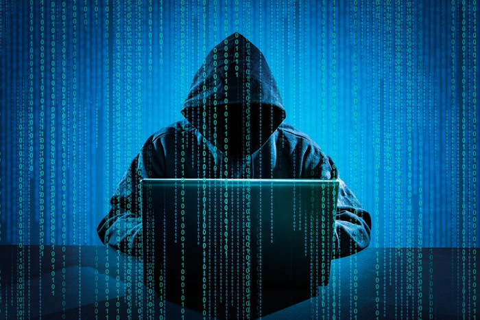 A person shrouded in a dark hood sitting in front of a computer