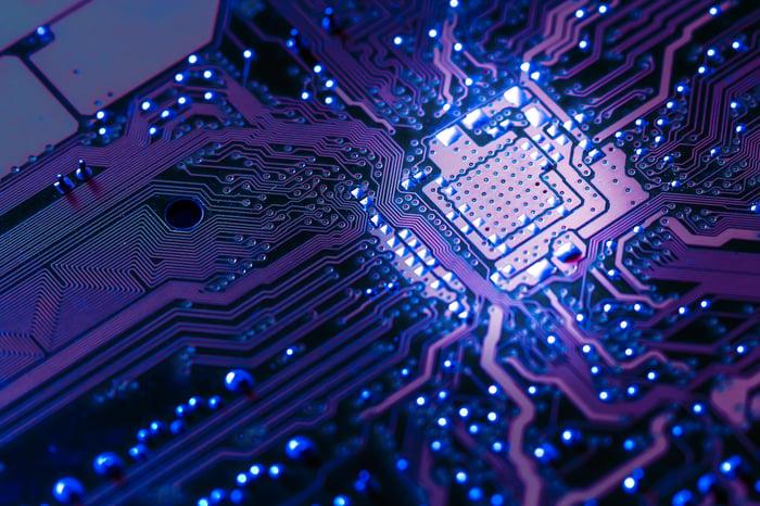 Computer circuit board glowing purple.