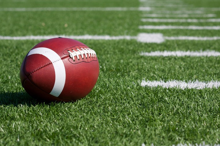 American football sitting on a green football field with white lines