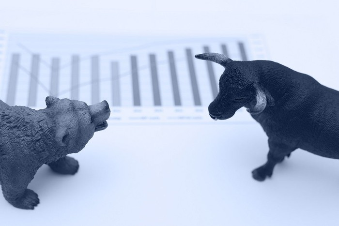 bull and bear standing in front of a rising chart.