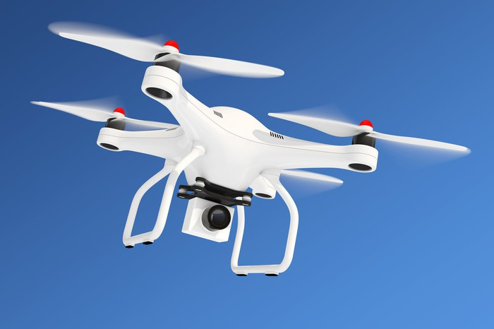 White drone equipped with camera flying in blue sky.