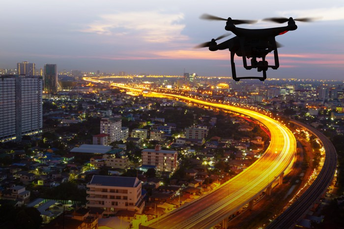 A drone flying over a city at dusk