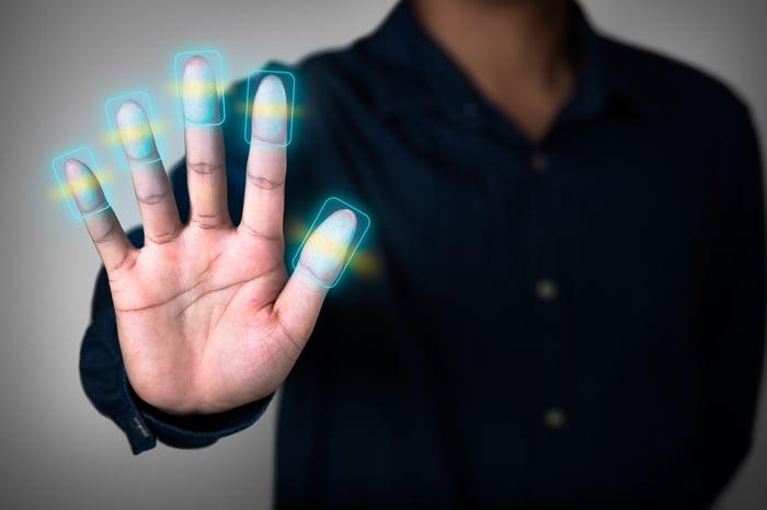 A person putting their hand out having their fingerprints digtally enhanced.