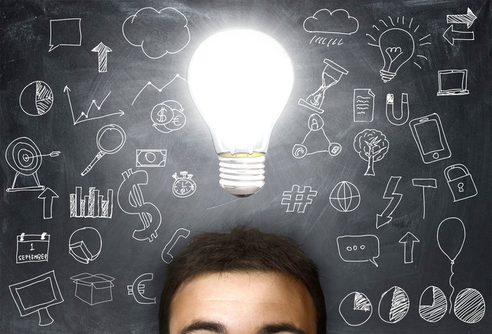 A light bulb shines brightly above someone who is standing in front of a chalk board covered by diagrams and hand-drawn charts.