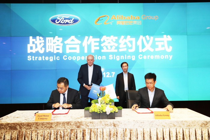 """Luo and Hu are seated at a table with documents; Hackett and Zhang are standing behind them, before a backdrop with the Ford and Alibaba logs and the words """"Strategic Cooperation Signing Ceremony"""" in Chinese and English."""