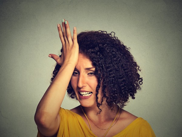 woman slapping forehead with regret mistake frustrated
