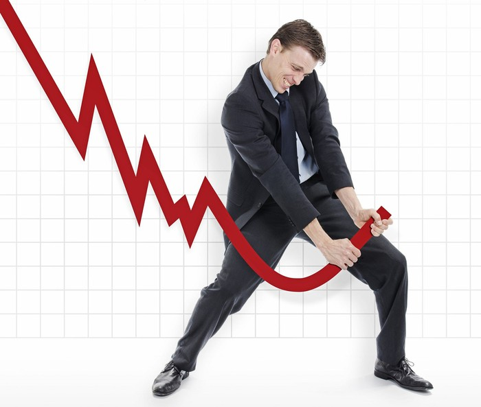 Man in suit struggling to reverse the course of a large downward sloping chart.