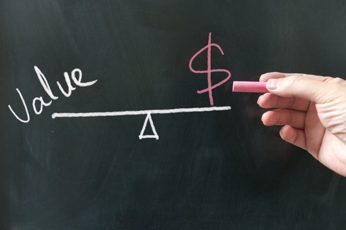 Chalk drawing of a scale with value written on one side of the fulcrum and a dollar sign on the opposite side.