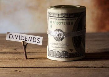 Roll of hundred dollar bills on table with dividends sign