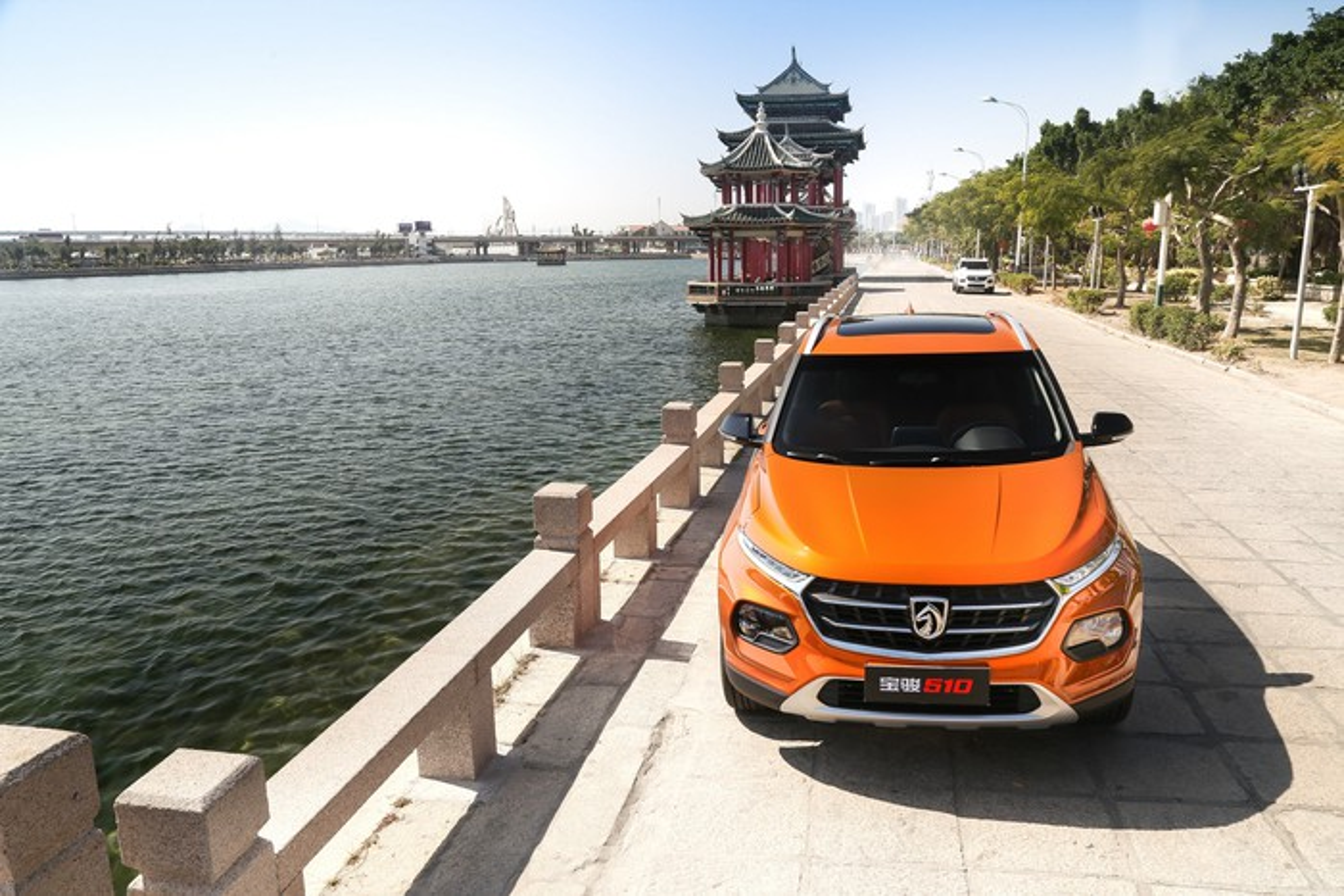 An orange Baojun 510, a small SUV, parked next to a river.