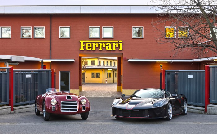 A 1947 Ferrari 125 Sport and a 2017 LaFerrari Aperta outside the historic entrance to Ferrari's headquarters in Maranello, Italy.